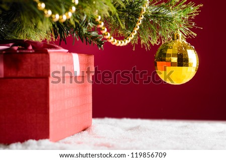 gift box on snow under christmas tree - stock photo