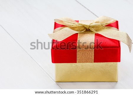 Gift box on the white wooden background - stock photo
