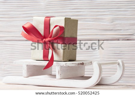Gift box on white sleigh over wooden background