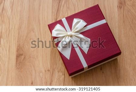 Gift box on wood, burgundy colored box, white ribbon bow - stock photo
