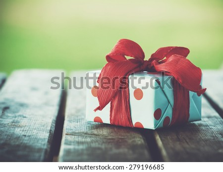 gift box on wooden table on natural background - stock photo