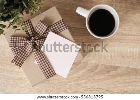 Gift box on wooden table top with space in blank paper for text and coffee, top view