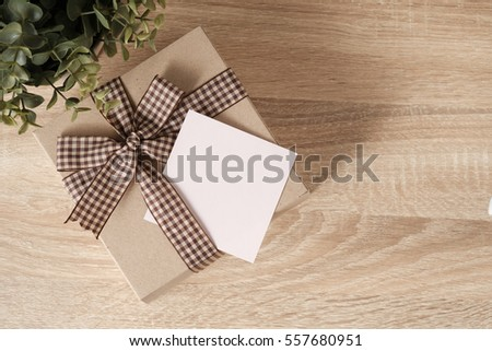 Gift box on wooden table top with space in blank paper for text, top view
