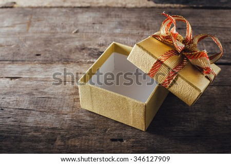 Gift box open on wooden table - stock photo