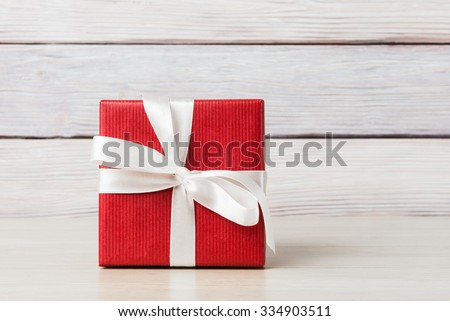 Gift box over light wooden background