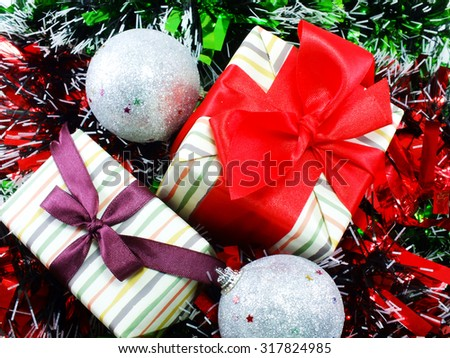 gift box present with red ribbon decorations with red and white tinsel christmas background - stock photo