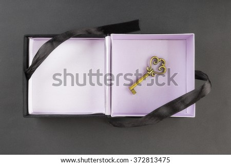 Gift box with a key at the bottom on a black background