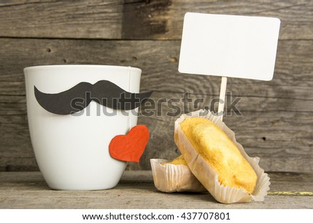 Gift box with a tag and a cup of coffee (tea), red heart, special cupcake and bow tie on wooden table. pad for text - stock photo