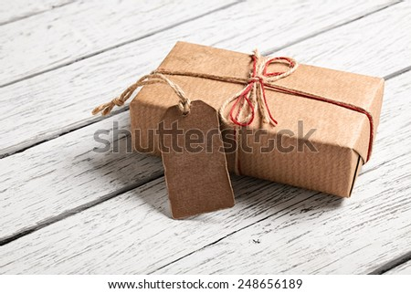 Gift box with blank gift tag on white wooden background. - stock photo