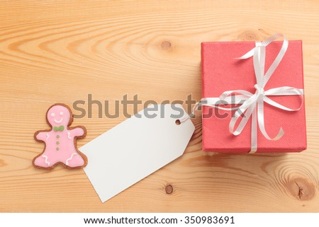 Gift box with blank paper tag and little gingerbread man cookie on wooden background - stock photo