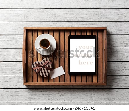 Gift box with blank tag, cup of coffee and digital tablet pc on salver on white wood table. - stock photo