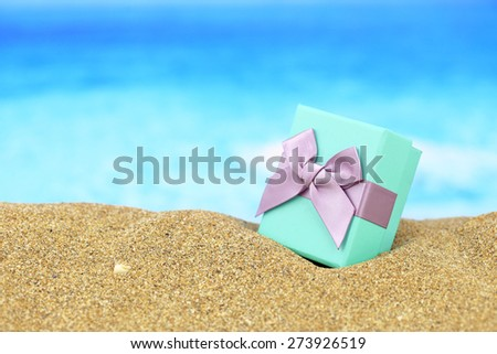 Gift box with bow on the sand - stock photo