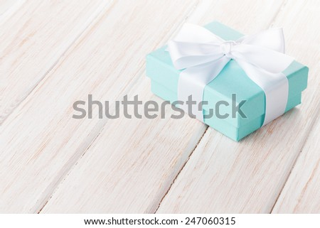 Gift box with bow over white wooden table with copy space - stock photo