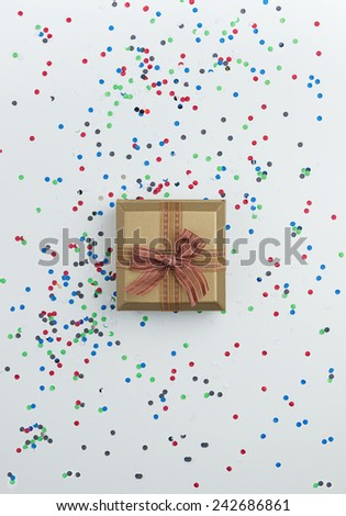 Gift box with confetti over white table - stock photo