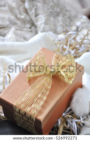 Gift box with golden ribbon put on scarf background