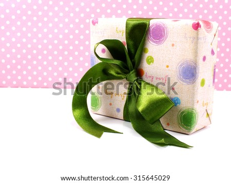 gift box with green bow on white and sweet polka dot background - stock photo