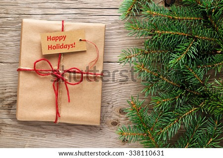 Gift box with happy holidays text on tag and fir branches - stock photo