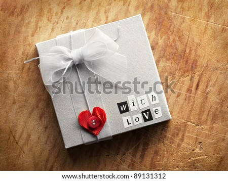 Gift box with heart shape and love text tied with organza ribbon on old vintage wooden background. - stock photo
