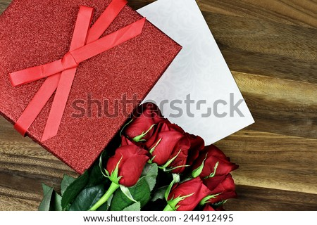 Gift box with long stem red roses and card over an old wooden background with room for copyspace. - stock photo