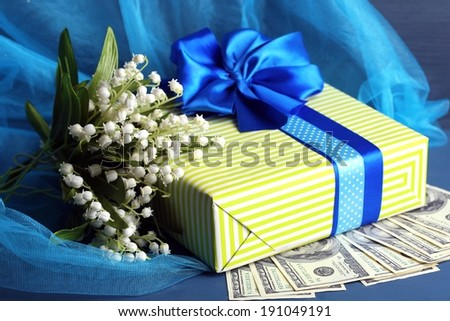 Gift box with money and flowers on color wooden background - stock photo