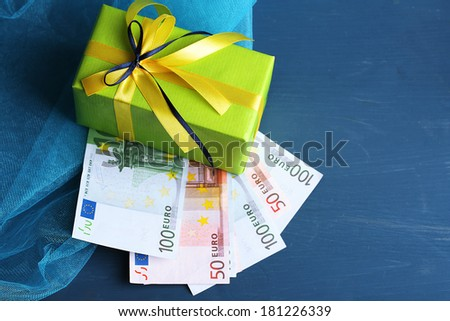 Gift box with money  on color wooden background - stock photo