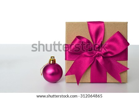 Gift box with pink ribbon and pink Christmas ball