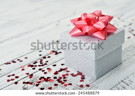 Gift box with red bow and confetti in shape of heart on wooden background - stock photo