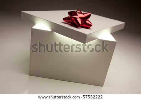 Gift Box with Red Bow Lid Revealing Very Bright Contents on a Gradated Background. - stock photo