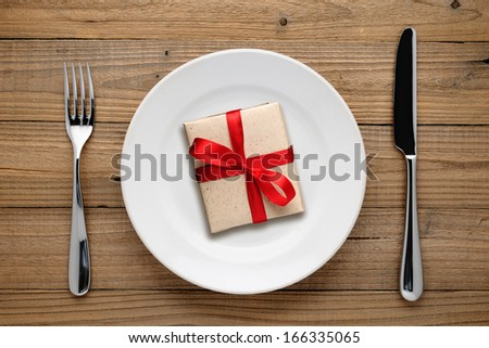 Gift box with red bow on plate on wooden background - stock photo