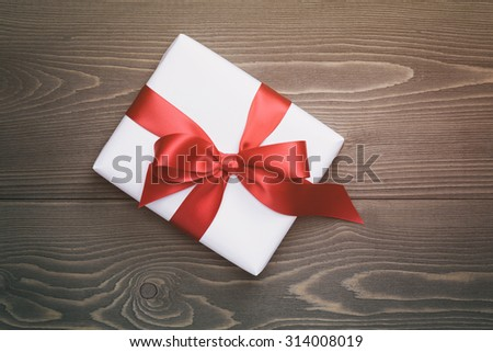 gift box with red bow on rustic table,vintage toned photo