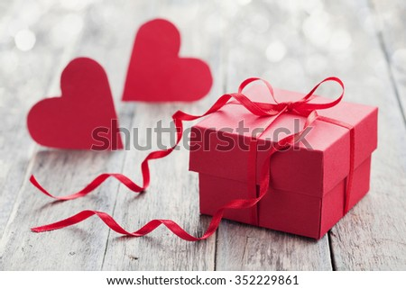 Gift box with red bow ribbon and two paper heart on wooden background for Valentines day - stock photo
