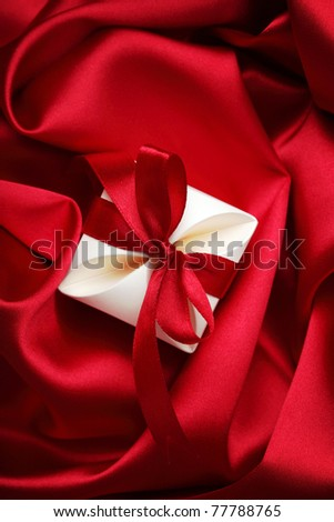 gift box with red ribbon bow on silk background - stock photo