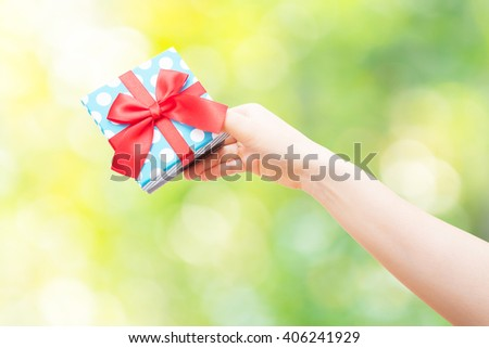 gift box with red ribbon in hand on nature background - stock photo
