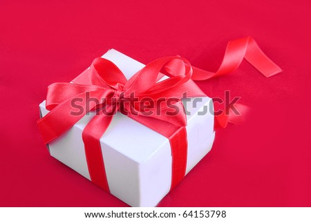 Gift-box with red ribbon on red background