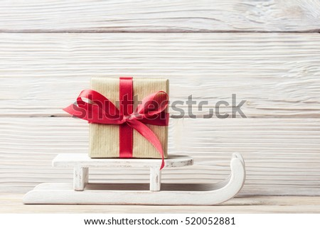 Gift box with red ribbon on sled over old wooden background