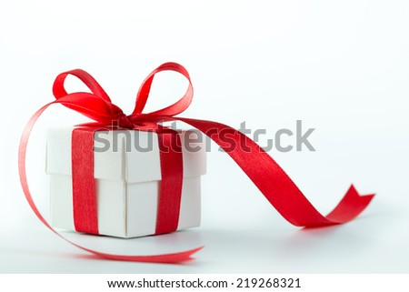 Gift box with red ribbon on white background - stock photo