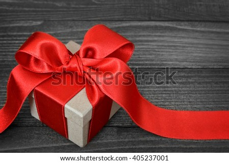 Gift box with red ribbon on wooden background