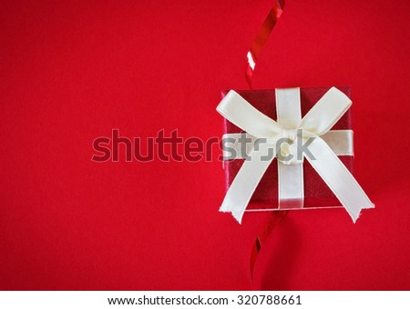 gift box with ribbon on a red background. festivals and events. top view. copy space background