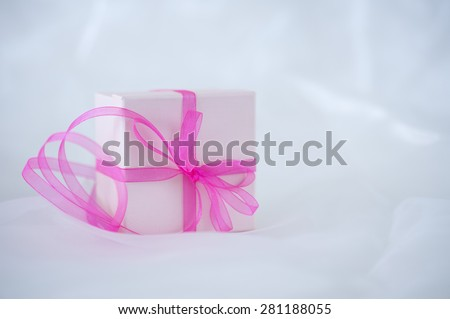Gift box with ribbon on cloth background - stock photo