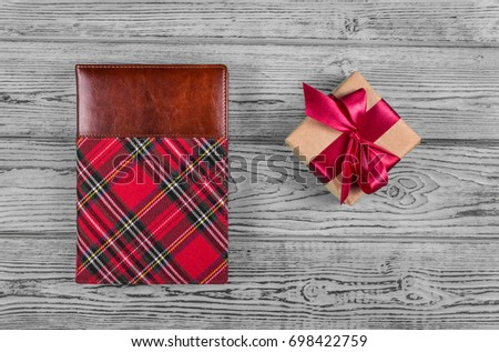 Gift box with satin ribbon and notepad in a cage on a gray background. Copy space