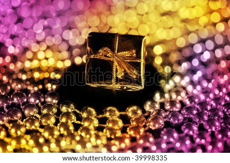 Gift box with shiny beads against black background - stock photo