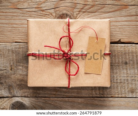Gift box with tag close-up on wooden background - stock photo