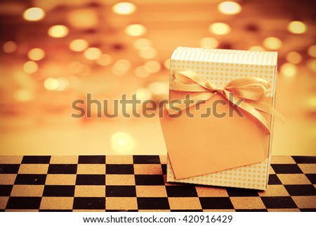gift box with tag on chessboard floor with blur perspective  bokeh  in shopping mall background - stock photo