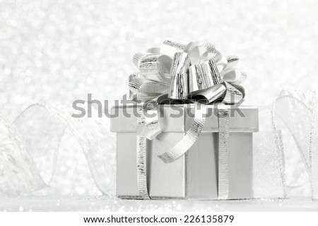 Gift box with tied to bow satin ribbon over bokeh background - stock photo