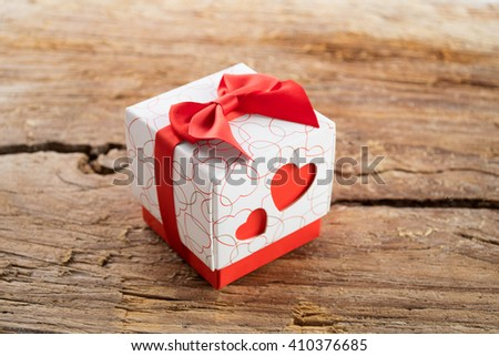 Gift box with two red hearts on side and red ribbons on wooden background