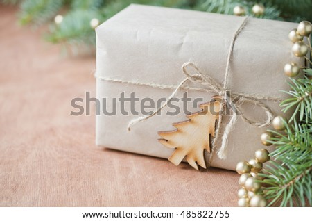 Gift box wrapped in plain brown paper, tied with string with a small wooden Christmas tree on a wooden table and a pine branch.Rustic style. Selective focus, space for text.