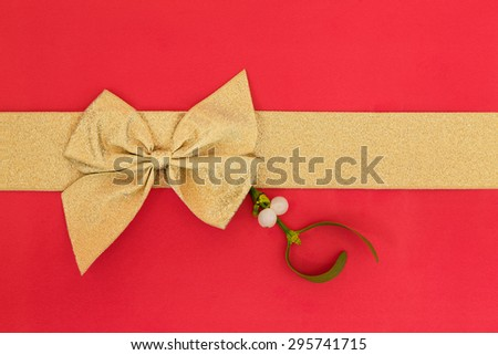 Gift box wrapping with gold ribbon and bow with mistletoe over red background. - stock photo