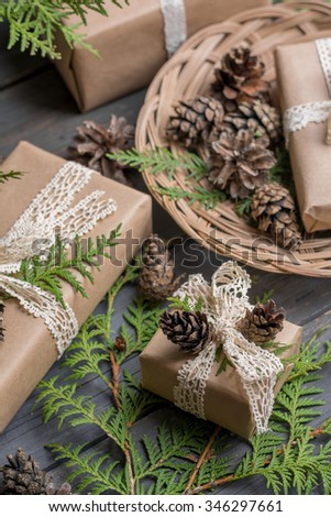 Gift boxes decorated lace bow, branches of thuja and cones on wooden table - stock photo