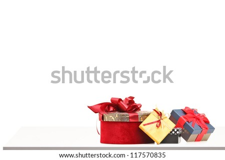 Gift boxes of various sizes and colors on a table isolated on white background - stock photo