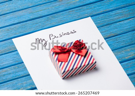 Gift boxes, pencil and paper with My Business words on blue background